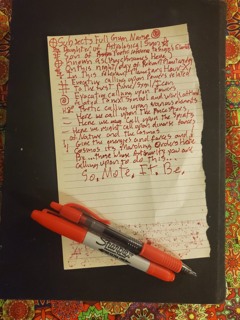 """A page torn from a lined journal, with text in red ink.  The Page lays upon a black book, which in turn lays upon a wildly patterned cloth in mostly yellow and orange tones with pops of purple and green.  the caption below reads """"A tongue firmly planted in cheek example of a Red Letter""""  The text in the Picture has random symbols alongside several of the lines of text, standing in for various magical and occult symbols.  The red text upon the pictured page reads """"Subjects Full Given Name.  Daughter of Astrological Sign. Sone of Poetic reference to Sign's Element. Known as (nicknames here).  On this Night/Day of relevant planetary day.  In this relevant planetary hour.  Evocative calling upon Powers related to the first Rune/Sigil/Icon. Evocative Calling upon Powers related to next Symbol and work at hand.  Poetic Calling upon various elements.  Here we call upon the Ancestors.  Here we call upon the Spirits.  Here we might call upon divers forces of Nature and the Cosmos.  Give the energies and forces and Cosmos it's Marching Orders Here.  By...Whose Authority are you calling upon to do this...  So.  Mote.  It.  Be"""""""